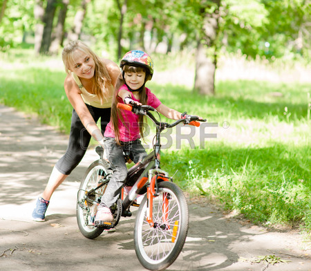 30941329-happy-mother-teaches-his-daughter-to-ride-a-bike
