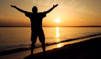man_on_beach_praising_God_-425x250